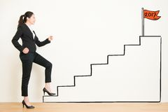 Side view of businesswoman climbing the stairs of drawing. View of businesswoman climbing the stairs of drawing to 2017. Concept of success and achieving your Royalty Free Stock Image