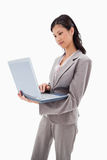 Side view of businesswoman standing with laptop Royalty Free Stock Images