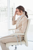 Side view of businesswoman suffering from headache in office Royalty Free Stock Image