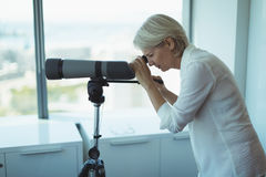 Side view of businesswoman using telescope. While standing by window in office Royalty Free Stock Photography
