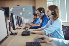 Side view of businesswoman working at call center royalty free stock images