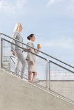 Side view of businesswomen moving down stairs against sky Royalty Free Stock Photography