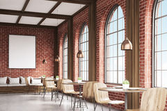 Side view of cafe with chairs, brick. Side view of cafe with chairs standing near small round tables and a sofa near a brick wall with a poster hanging above it Royalty Free Stock Photos