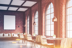 Side view of cafe with chairs, brick, toned. Side view of cafe with chairs standing near small round tables and a sofa near a brick wall with a poster hanging Royalty Free Stock Photo