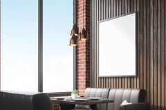 Side view of cafe interior with sofas. Side view of a cafe interior with a large window, leather sofas and small wooden tables. Vertical framed poster on a brick Royalty Free Stock Photo