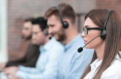 Side view.the call center operator and her colleagues work in the office. royalty free stock photography