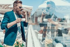Orderly unshaven male talking on phone outdoor. Side view calm bearded businessman speaking on mobile while looking at street. He drinking cup of beverage during Royalty Free Stock Photo