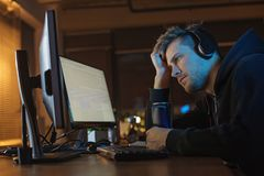 Serene male working with computer at night. Side view calm programmer looking at screen of gadget while listening music. He tasting can of energy liquid. Job Stock Image