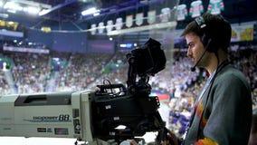 Side view cameraman works at hockey game on spectator places. Kazan, Tatarstan Russia - December 26 2018: Side view professional cameraman works with shooting stock footage