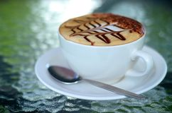 Side view of cappuccino coffee cup with spoon Stock Images