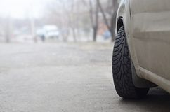 A side view of a car standing near a roadway. A passenger car stands on the asphalt of a suburban road. Concept of driving a car Royalty Free Stock Photos
