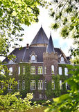 Side view of Castle Linnep. Germany. Ancient water castle with turrets and view through trees to the castle on a sunny day.n Royalty Free Stock Photo