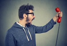 Angry man screaming at phone receiver. Side view of casual bearded man holding red telephone receiver and yelling in anger Stock Photography