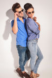 Side view of a casual couple posing near a  wall Stock Photography