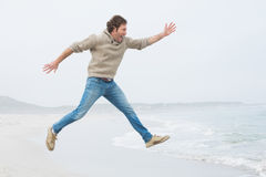 Side view of a casual man jumping at beach Royalty Free Stock Images