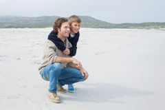 Side view of a casual man and son relaxing at beach Royalty Free Stock Image