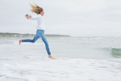 Side view of a casual woman jumping at beach Stock Photo