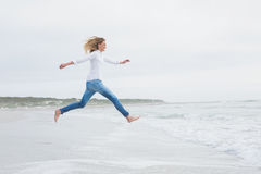 Side view of a casual woman jumping at beach Stock Photos