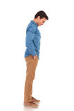 Side view of a casual young man looking down. To something standing with hands in pockets Royalty Free Stock Photo