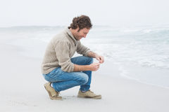 Side view of a casual young man relaxing at beach Royalty Free Stock Photo