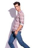 Man steps with hands in pockets. Side view of casual young man stepping and looking at the camera with his thumbs in his pockets. isolated on white background Royalty Free Stock Image