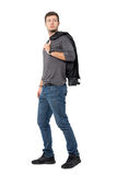 Side view of casual young man walking with jacket over shoulder looking behind Royalty Free Stock Photography