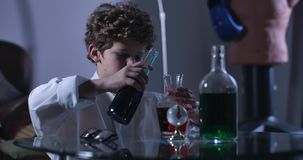 Side view of Caucasian boy mixing multi-colored liquids in flasks. Curly-haired teenage genius in lab coat holding