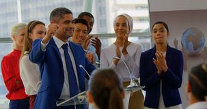 Businessman standing at podium with colleagues in the business seminar 4k. Side view of a Caucasian businessman standing on the podium and  celebrating success stock video
