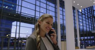 Businesswoman talking on mobile phone in the lobby at office 4k. Side view of caucasian businesswoman talking on mobile phone in the lobby at office. She is stock video
