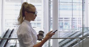 Side view of caucasian businesswoman using mobile phone and drinking coffee in the lobby at office 4. Side view of caucasian businesswoman using mobile phone and stock video footage