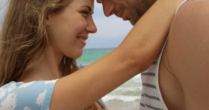 Side view of Caucasian couple embracing each other on the beach 4k. Side view of Caucasian couple embracing each other on the beach. They are spending time stock footage