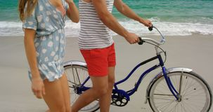 Side view of Caucasian couple walking with bicycle on the beach 4k. Side view of Caucasian couple walking with bicycle on the beach. They are interacting with stock video footage