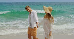 Side view of Caucasian couple walking hand in hand on the beach 4k. Side view of Caucasian couple walking hand in hand on the beach. They are spending time stock video