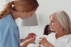 Female doctor talking to disabled active senior woman about her hearing aid on bed in bedroom. Side view of Caucasian female doctor talking to disabled active stock photos