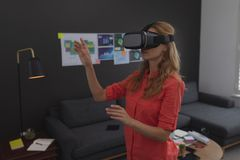 Female executive using virtual reality headset. Side view of Caucasian female executive using virtual reality headset in office stock image