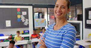 Side view of Caucasian female teacher standing with arms crossed in the classroom 4k. Side view of Caucasian female teacher standing with arms crossed in the stock video footage