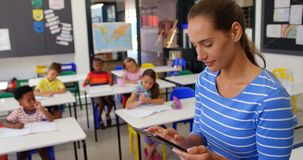 Side view of Caucasian female teacher using digital tablet in the classroom 4k. Side view of Caucasian female teacher using digital tablet in the classroom stock video