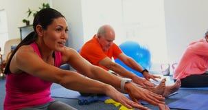 Side view of Caucasian female trainer training senior man in exercising at fitness studio 4k stock video