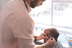Male doctor applying hearing aid to senior man ear. Side view of a Caucasian male doctor applying hearing aid to an African senior men ear in clinic stock photography