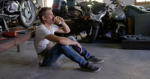 Male mechanic drinking coffee in motorbike repair garage 4k. Side view of Caucasian male mechanic drinking coffee in motorbike repair garage. He is looking away stock video footage