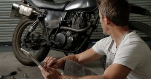 Male mechanic using digital tablet in motorbike repair garage 4k. Side view of Caucasian male mechanic using digital tablet in motorbike repair garage. He is stock video