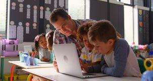 Side view of Caucasian male teacher teaching schoolkids on laptop in the classroom 4k. Side view of Caucasian male teacher teaching schoolkids on laptop in the stock video footage
