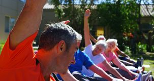 Side view of Caucasian male trainer training senior people in performing exercise at the garden of n stock footage