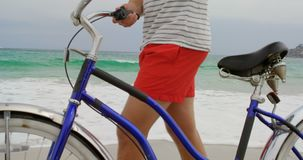 Side view of Caucasian man walking with bicycle on the beach 4k. Side view of Caucasian man walking with bicycle on the beach. Beautiful sky and calm sea in the stock video footage