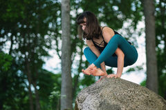 Side view of caucasian practicing yoga, standing in hand balance exercise, Bakasana pose. Working out on big stone in nature Stock Image