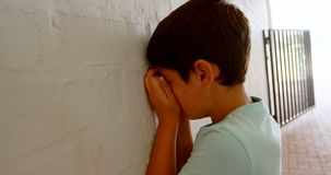 Side view of Caucasian schoolboy covering his face with hands while leaning on wall in corridor 4k. Side view of Caucasian schoolboy covering his face with hands stock footage