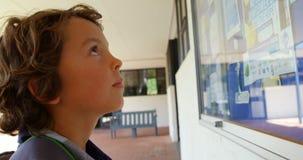 Side view of Caucasian schoolboy looking at noticeboard in the school corridor 4k. Side view of Caucasian schoolboy looking at noticeboard in the school corridor stock footage