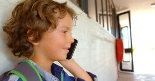 Side view of Caucasian schoolboy talking on mobile phone in school corridor 4k. Side view of Caucasian schoolboy talking on mobile phone in school corridor. He stock footage