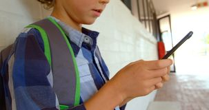 Side view of Caucasian schoolboy using mobile phone while leaning on wall in school corridor 4k. Side view of Caucasian schoolboy using mobile phone while stock footage
