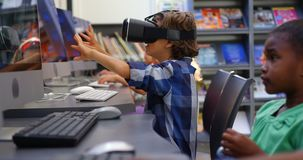 Side view of Caucasian schoolboy using virtual reality headset in the classroom 4k. Side view of Caucasian schoolboy using virtual reality headset in the stock video footage